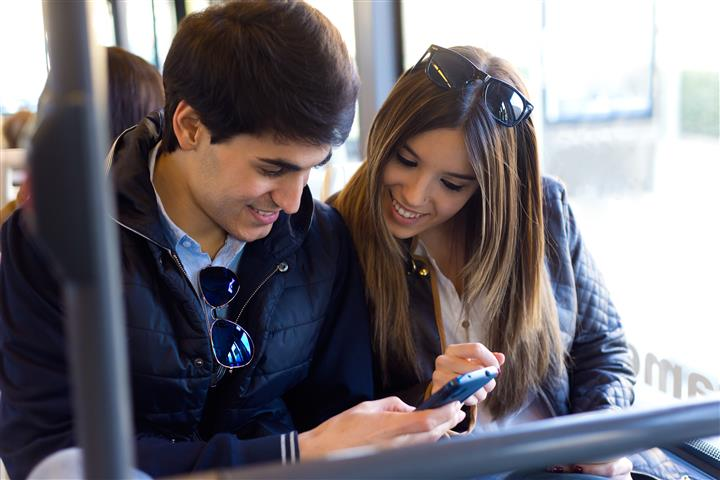 Portrait of young couple using mobile phone at bus.