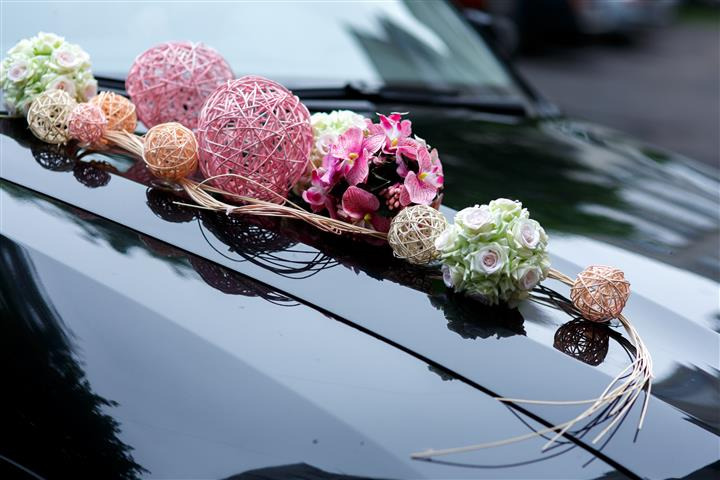 A stylish decoration of white flowers, ribbons and pink balls on a shiny wedding car